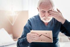 Uomo anziano triste che pulisce gli strappi assenti Fotografia Stock Libera da Diritti
