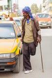 Uomo arabo anziano che utilizza le grucce accanto ad un taxi giallo nelle quiete CIT fotografia stock