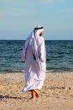 Uomo arabo che cammina dalla spiaggia fotografia stock libera da diritti