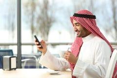 Uomo arabo che manda un sms in uno Smart Phone in una barra immagine stock libera da diritti