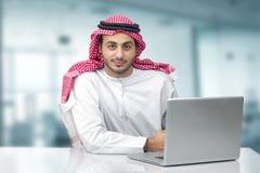 Uomo arabo di affari che utilizza taccuino nell'ufficio Fotografia Stock