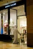 Uomo arabo di Emirati che entra in un negozio in un viale Immagine Stock