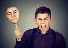 Uomo arrabbiato che decolla maschera con l'espressione calma del fronte Fotografie Stock