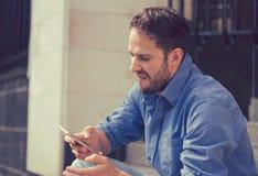 Uomo arrabbiato che esamina telefono cellulare che si siede sui punti fuori del complesso condominiale fotografie stock libere da diritti