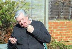 Uomo arrabbiato che per mezzo di un telefono cellulare. Immagini Stock