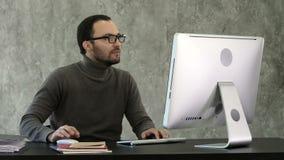 Uomo arrabbiato che si siede alla tavola con il computer sopra fondo grigio stock footage