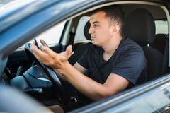 Uomo arrabbiato che si siede in automobile con mandare un sms disponibile del telefono cellulare mentre guidando Distracted ha co fotografia stock