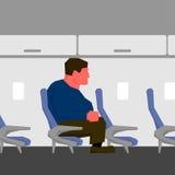 Uomo arrabbiato con il viso arrossato, troppo grande per il sedile sull'aereo Fotografia Stock