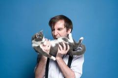Uomo arrabbiato con la bocca aperta che tiene e che guarda al gatto grigio e bianco sveglio fotografie stock