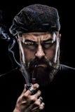 Uomo arrabbiato con una barba spessa che fuma un tubo Fotografie Stock Libere da Diritti