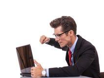 Uomo arrabbiato di affari al suo computer portatile Immagine Stock