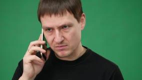 Uomo arrabbiato di affari che grida sul telefono cellulare delle cellule isolato sopra fondo verde stock footage