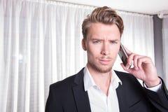 Uomo arrabbiato di affari del ritratto giovane in vestito sul telefono Fotografia Stock