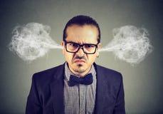 Uomo arrabbiato di affari, vapore di salto che esce dalle orecchie, circa per avere esaurimento nervoso fotografia stock libera da diritti