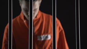 Uomo arrestato in vestito arancio che si avvicina alle barre della prigione, giudizio di pena di morte stock footage