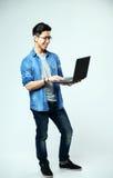 Uomo asiatico allegro che per mezzo del computer portatile Fotografia Stock Libera da Diritti