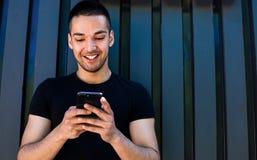 Uomo asiatico allegro facendo uso del messaggero fotografia stock
