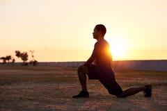Uomo asiatico atletico che allunga le sue gambe prima di un funzionamento di mattina Fotografia Stock Libera da Diritti