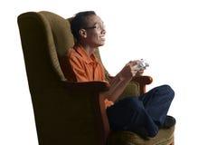 Uomo asiatico attraente del nerd che gioca gioco con gamepad sul sofà Fotografia Stock Libera da Diritti