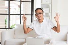 Uomo asiatico bello che per mezzo del computer della compressa Immagini Stock