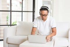 Uomo asiatico bello che per mezzo del computer della compressa Fotografia Stock