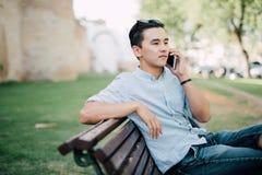 Uomo asiatico bello che si siede sul banco e che parla sul telefono Immagini Stock Libere da Diritti