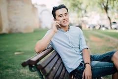 Uomo asiatico bello che si siede sul banco e che parla sul telefono Fotografia Stock Libera da Diritti