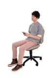 Uomo asiatico che ascolta sul suo telefono cellulare Fotografie Stock Libere da Diritti