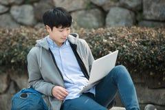 Uomo asiatico che backpacking facendo uso del computer portatile Immagini Stock Libere da Diritti