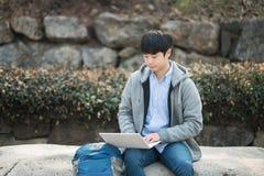 Uomo asiatico che backpacking facendo uso del computer portatile Fotografia Stock Libera da Diritti
