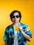 Uomo asiatico che beve Juice Wearing Sunglasses arancio contro Yello Fotografie Stock Libere da Diritti