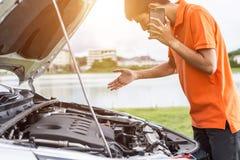 Uomo asiatico che chiama e che controlla la sua automobile nociva Per la riparazione c dell'automobile Fotografie Stock Libere da Diritti