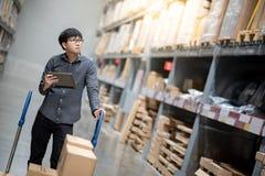 Uomo asiatico che fa inventario sulla compressa in magazzino fotografie stock libere da diritti