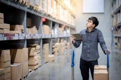 Uomo asiatico che fa inventario sulla compressa in magazzino immagine stock libera da diritti