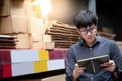 Uomo asiatico che fa inventario sulla compressa in magazzino immagine stock