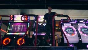 Uomo asiatico che gioca il gioco di rivoluzione di ballo e che balla su Arcade Machine Pad nel centro commerciale di zona MBK del video d archivio