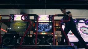 Uomo asiatico che gioca il gioco di rivoluzione di ballo e che balla su Arcade Machine Pad nel centro commerciale di zona MBK del stock footage