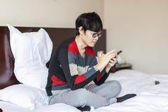 Uomo asiatico che gioca telefono sul letto Fotografie Stock Libere da Diritti