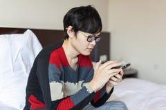 Uomo asiatico che gioca telefono sul letto Fotografia Stock Libera da Diritti