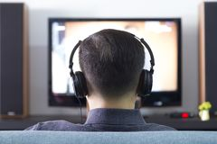 Uomo asiatico che indossa le cuffie nere che godono del home entertainment Fotografie Stock Libere da Diritti