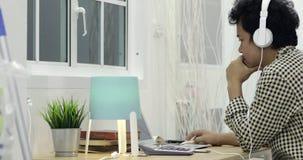 Uomo asiatico che lavora duro con il computer portatile a casa stock footage