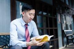 Uomo asiatico che legge un libro che si siede sul banco Fotografia Stock Libera da Diritti