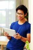 Uomo asiatico che per mezzo del computer della compressa Fotografie Stock Libere da Diritti