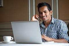 Uomo asiatico che per mezzo del telefono sul computer portatile Immagini Stock Libere da Diritti