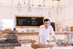 Uomo asiatico che porta una camicia bianca che sta nel negozio del forno Immagine Stock Libera da Diritti