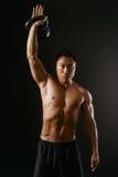 Uomo asiatico che risolve con la campana del bollitore Fotografia Stock