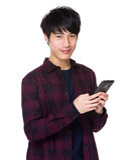 Uomo asiatico che scrive un messaggio a macchina sul telefono cellulare Fotografia Stock