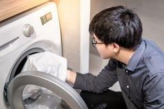 Uomo asiatico che seleziona i vestiti dalla lavatrice fotografie stock