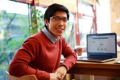 Uomo asiatico che si siede alla tavola con il computer portatile fotografie stock libere da diritti