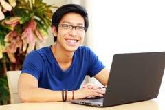 Uomo asiatico che si siede alla tavola con il computer portatile Immagine Stock